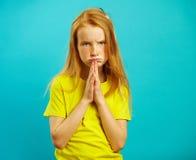 有哀伤的眼睛的女孩要求买她某事,在胸口棕榈的被折叠的手,表达请求,有乞求神色 免版税库存照片