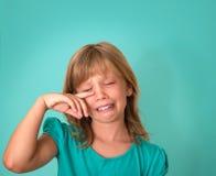 有哀伤的表示和泪花的小女孩 绿松石背景的哭泣的孩子 情感 免版税库存照片