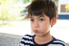 有哀伤的面孔的小男孩临时替人照看孩子的人 免版税图库摄影