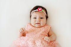 有哀伤的面孔的逗人喜爱的女婴在一条白色毯子说谎 库存照片