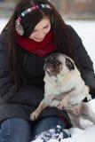 有哈巴狗小狗的青少年的女孩在雪 免版税图库摄影