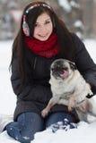 有哈巴狗小狗的青少年的女孩在雪 免版税库存图片