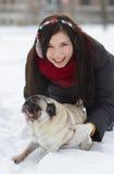 有哈巴狗小狗的青少年的女孩在雪 库存图片