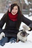 有哈巴狗小狗的青少年的女孩在雪 图库摄影