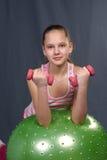 有哑铃和球体育的女孩 库存照片