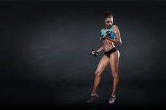 有哑铃的健身女孩在黑暗的背景 免版税库存照片