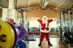 有哑铃的圣诞老人在圣诞节的健身房 库存图片
