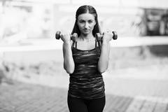 有哑铃的女孩允诺了健身 库存图片