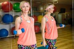 有哑铃的妇女在健身房 免版税图库摄影