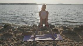 有哑铃的年轻运动美女在海的背景的手上 做锻炼与的健身女孩 股票视频