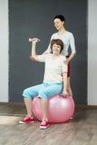 有哑铃的成熟妇女和年轻教练 免版税库存图片
