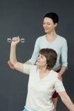 有哑铃的成熟妇女和年轻教练 图库摄影