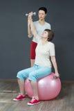 有哑铃的成熟妇女和年轻教练 库存照片