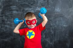有哑铃的男孩超级英雄 库存照片