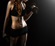 有哑铃的年轻美丽的健身妇女在黑色 库存图片