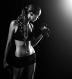 有哑铃的年轻美丽的健身妇女在黑色 免版税库存照片