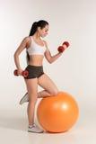 有哑铃的年轻美丽的女运动员行使在fitball的 免版税库存照片