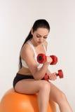 有哑铃的年轻美丽的女运动员行使在fitball的 库存照片