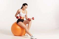 有哑铃的年轻美丽的女运动员行使在fitball的 图库摄影