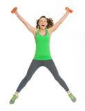 有哑铃跳跃的愉快的健康少妇 图库摄影