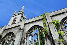 有哥特式窗口的一个美丽的老指向蓝天的教会和塔 免版税库存图片