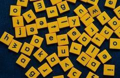 有哥特式黑体字的黄色瓦片在黑背景 免版税图库摄影