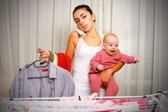 有哭泣的婴孩的疲乏的母亲在家 库存照片