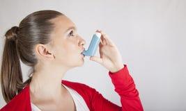 有哮喘吸入器的逗人喜爱的女孩 免版税库存图片