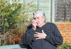 有哮喘吸入器的年长人。 免版税库存照片