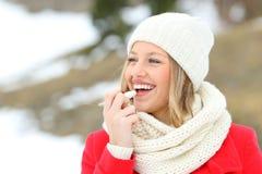 有唇膏的女孩保护的嘴唇在冬天 免版税库存照片