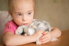有唐氏综合症的女孩拥抱兔子 免版税库存照片
