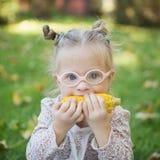 有唐氏综合症的美丽的女孩吃在自然的玉米 免版税库存照片