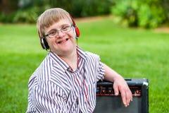有唐氏综合症佩带的耳机的男孩 免版税库存照片