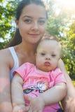 有唐氏综合症和他的年轻母亲的逗人喜爱的男婴在夏日 免版税库存图片