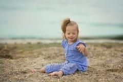 有唐氏综合症投掷的沙子的美丽的女孩在海滨 免版税库存图片