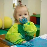 有唐氏综合症的小女孩是繁忙的绘画 图库摄影