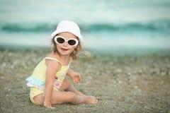 有唐氏综合症的快乐的小女孩与基于沿海的玻璃 免版税库存照片