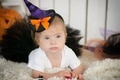 有唐氏综合症的美丽的小女孩在衣服一个小巫婆 库存图片