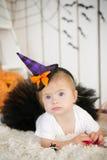 有唐氏综合症的美丽的小女孩在衣服一个小巫婆 免版税库存图片