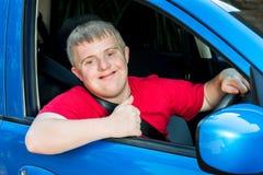 有唐氏综合症的年轻司机在汽车 T 免版税库存图片