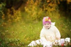 有唐氏综合症的滑稽的美丽的女孩在秋天公园 免版税库存图片