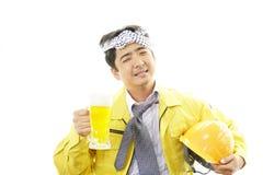 有啤酒杯的微笑的工作者 免版税库存照片
