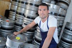 有啤酒桶的工作者在啤酒厂 免版税库存照片