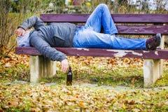 有啤酒瓶的人睡觉在一条长凳的在公园 库存照片