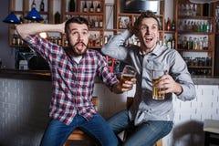 有啤酒观看的橄榄球的青年人在酒吧 库存照片
