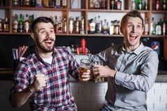 有啤酒观看的橄榄球的青年人在酒吧 免版税图库摄影