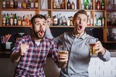 有啤酒观看的橄榄球的青年人在酒吧 库存图片