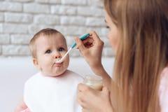 有喂养一点婴孩的匙子的年轻母亲 库存图片
