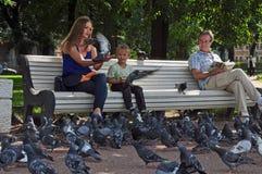 有喂小孩鸽子的女孩 免版税库存图片