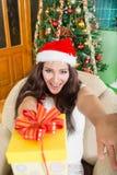 有喜悦和宽厚的愉快的少妇提供的礼物盒 免版税库存照片
